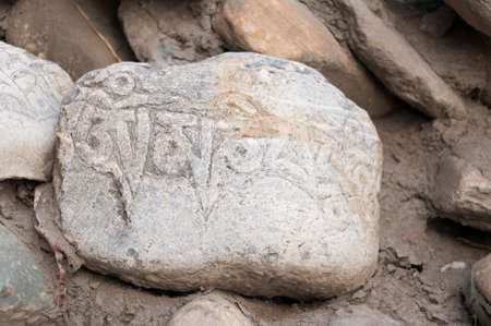 devotional: Mani stone, prayer stones with Buddhist symbols in the Annapurna area, Nepal. Stock Photo