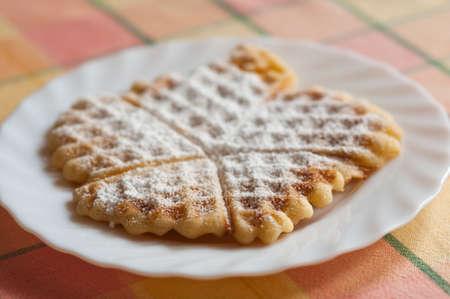 powdered sugar: Waffle with powdered sugar on a plate.