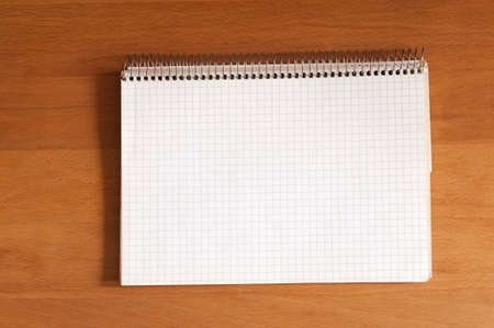 spiral notebook: Spiral notebook of graph paper with copy space in front of wooden background. Stock Photo