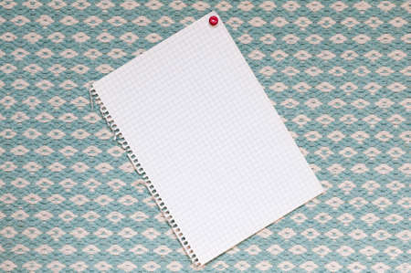 squared: Memo from squared paper with copy space against a blue woven fabric.