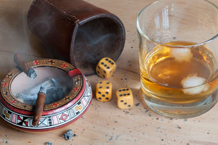 alcoholic beverage: Dice game with cigar and alcoholic beverage.