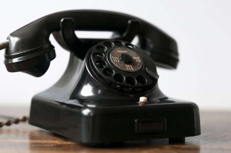 telecommunications equipment: Old black phone on a desk and white background. Stock Photo