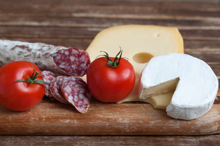 delicadeza: Delicadeza mediterr�nea, salami y queso con tomate rojo como fondo de alimentos.