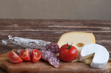 delicacy: Mediterranean delicacy, salami and cheese with red tomato as food backgrounds. Stock Photo