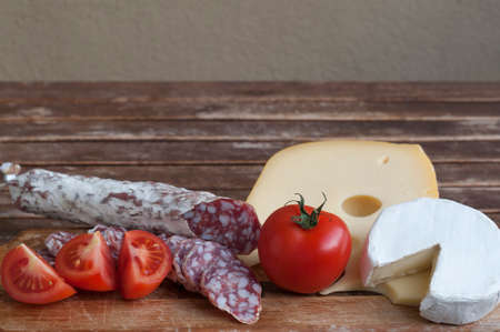 manjar: Mediterranean delicacy, salami and cheese with red tomato as food backgrounds. Foto de archivo