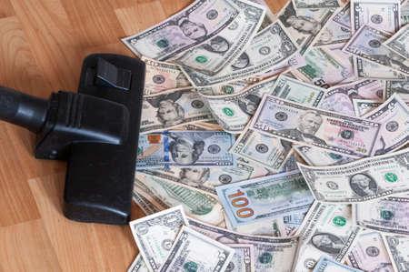 sucks: Vacuum cleaner sucks on U.S. dollars.
