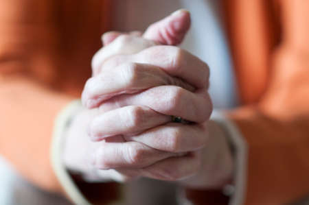 clasped: Old woman holding hands clasped in prayer.