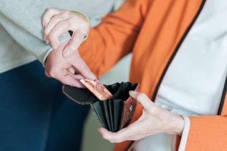 damas antiguas: Una mujer toma dinero de la carpeta abierta a las mujeres mayores. El Senior los mantiene por el brazo.