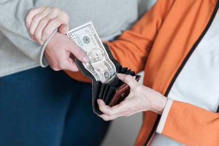 criminal activity: A woman takes money from open wallet a Senior women. The Senior keeps them by the arm. Stock Photo