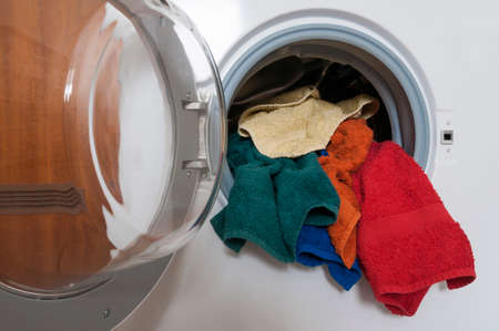 dry cleaned: Housework, laundry service, washing machine with colored laundry.