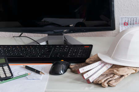 place of employment: Desk of a construction company with hardhat and work gloves computer. Stock Photo