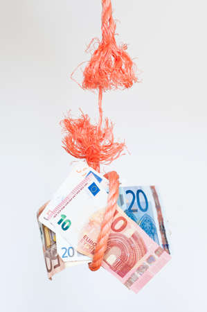 ordeal: A rope hangs with Euro bank notes only by a thread. Stock Photo