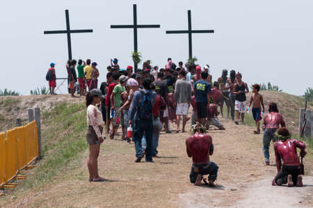 flagellation: San Fernando , Luzon, Philippines, March 25, 2016: Easter procession in the city of San Fernando, Luzon Island, Philippines. Flagellants who mortify themselves on Good Friday on a field.