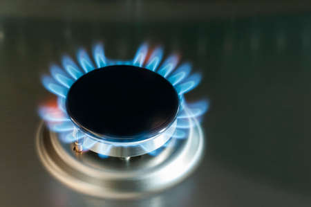 Gas flame of a gas stove in stainless steel. Stock Photo