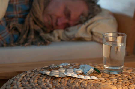 sleeping pills: A man lying with cold in bed lying in front of him medicines, selective focus.