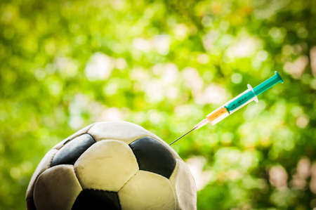 Soccer ball gets an injection with a syringe, doping in sports.