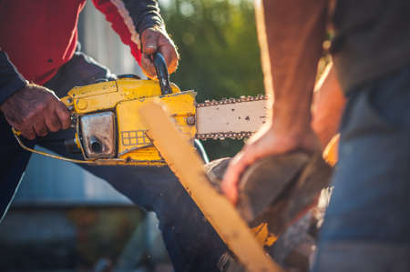 Cutting wood with Chainsaw .