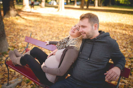 Young happy couple sitting on a bench in the city park daydreaming about the future.