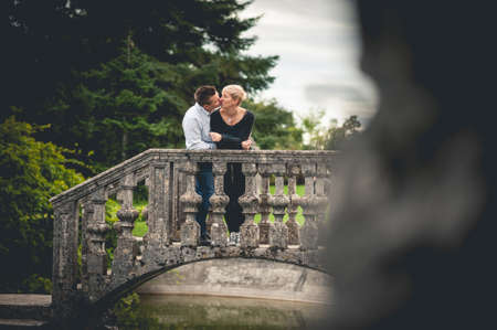 two stroke: Young couple leaning on railing of bridge Stock Photo