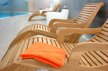 elbowchair: Sunbeds in the fitness with one orange towel near the pool