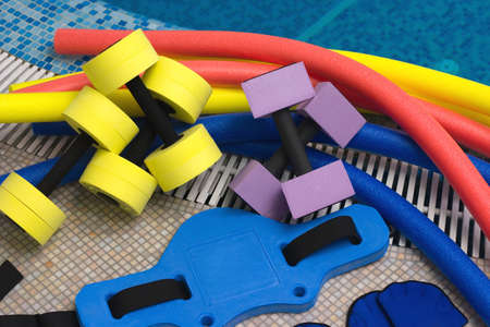 hydrotherapy: aqua noodles dumbbells belt  for aqua aerobics lie on the coast in pool