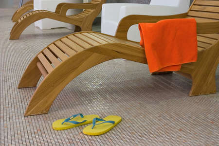 elbowchair: sunbed with orange towel on the armrest and yellow sandals near Stock Photo