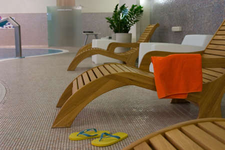 elbowchair: Sunbeds in the fitness near swimming pool with plants