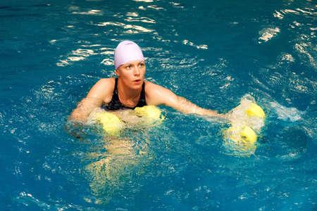 La ragazza è impegnata acqua gym con manubri Archivio Fotografico - 3751421