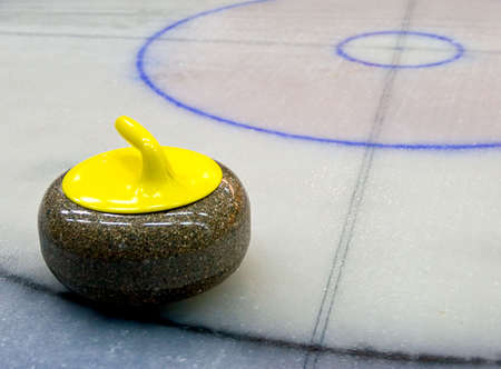 curling: yellow granite stone for curling game on the ice (close-up)