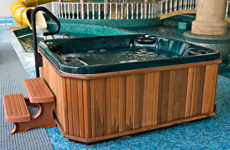 Bath from a jacuzzi with steps near swimming pool Archivio Fotografico
