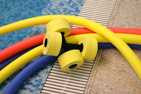 water aerobics equipment - noodles and dumbells Stock Photo