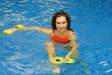Woman is engaged aqua aerobics in water photo
