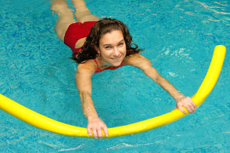 jonge vrouw is zwemmen met aqua noedels