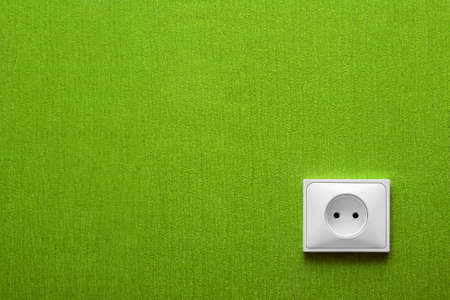 The electric socket in a green wall in the corner photo