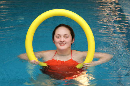 Woman is engaged in aerobics in water with  aqua noodles