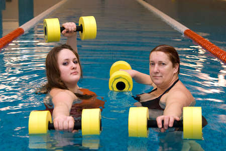 water aerobics: A senior women and young woman in water with dumbbells Stock Photo