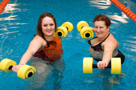 aerobic training: Mum with a daughter are engaged in aqua aerobics Stock Photo