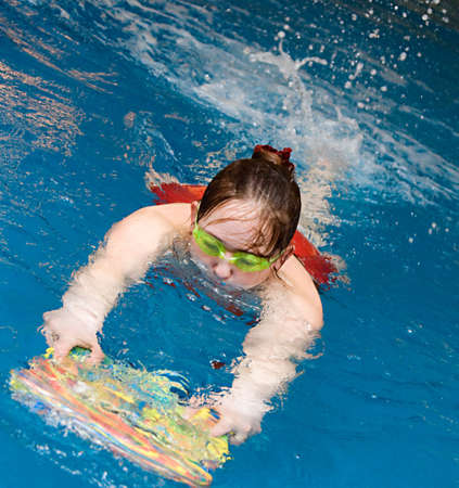 swimm: girl learn to swimm with board in the swimming pool Stock Photo