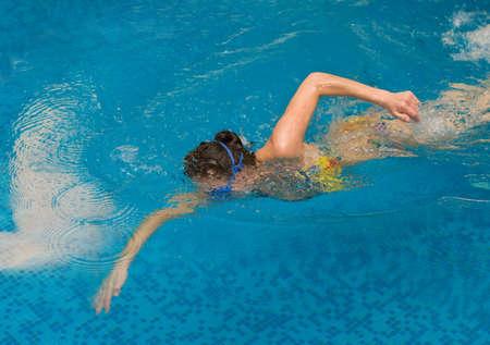 운동 선수는 수영장에서 크롤링을 수영합니다.