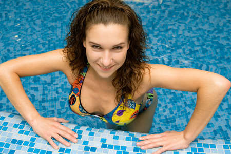 beautiful girl at a side in swimming pool looks up photo