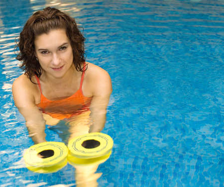Woman is engaged aqua aerobics in water picture with space on the right