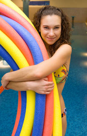 armful: girl holds aqua noodles armful standing near the swimming pool Stock Photo