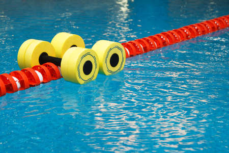 Floating aqua aerobics dumbbells in swimming pool