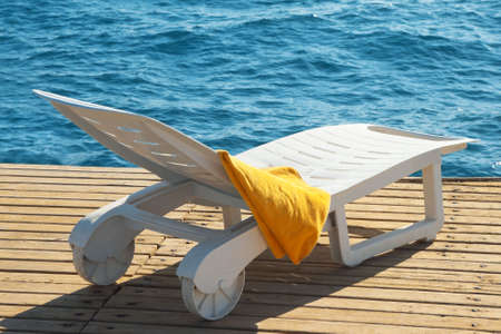 sunbed near the sea with a yellow towel  Stock Photo