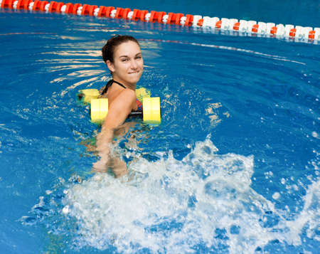aqua aerobic, woman in water with dumbbells splashes water