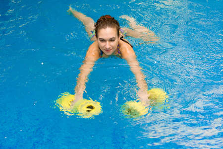aqua aerobic, woman in water with dumbbells Stock Photo - 5719076