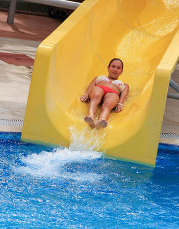 Young woman riding down on waterslide in aqua park