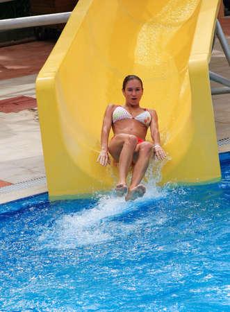 Girl slide down on waterslide in aqua park photo