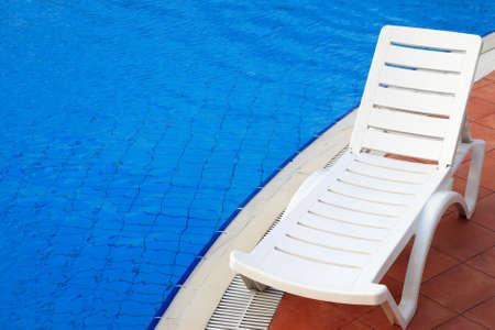 lounge stoelen in een zwembad nodigen u uit om te ontspannen