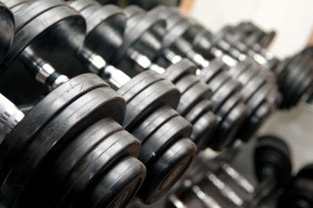 Barbells at the gym. Black rubber dumbbells, closeup view